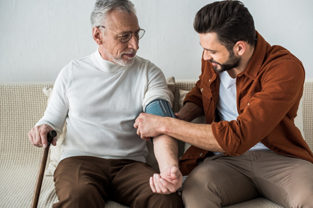 Young male family caregiver assisting older man with a blood pressure monitor