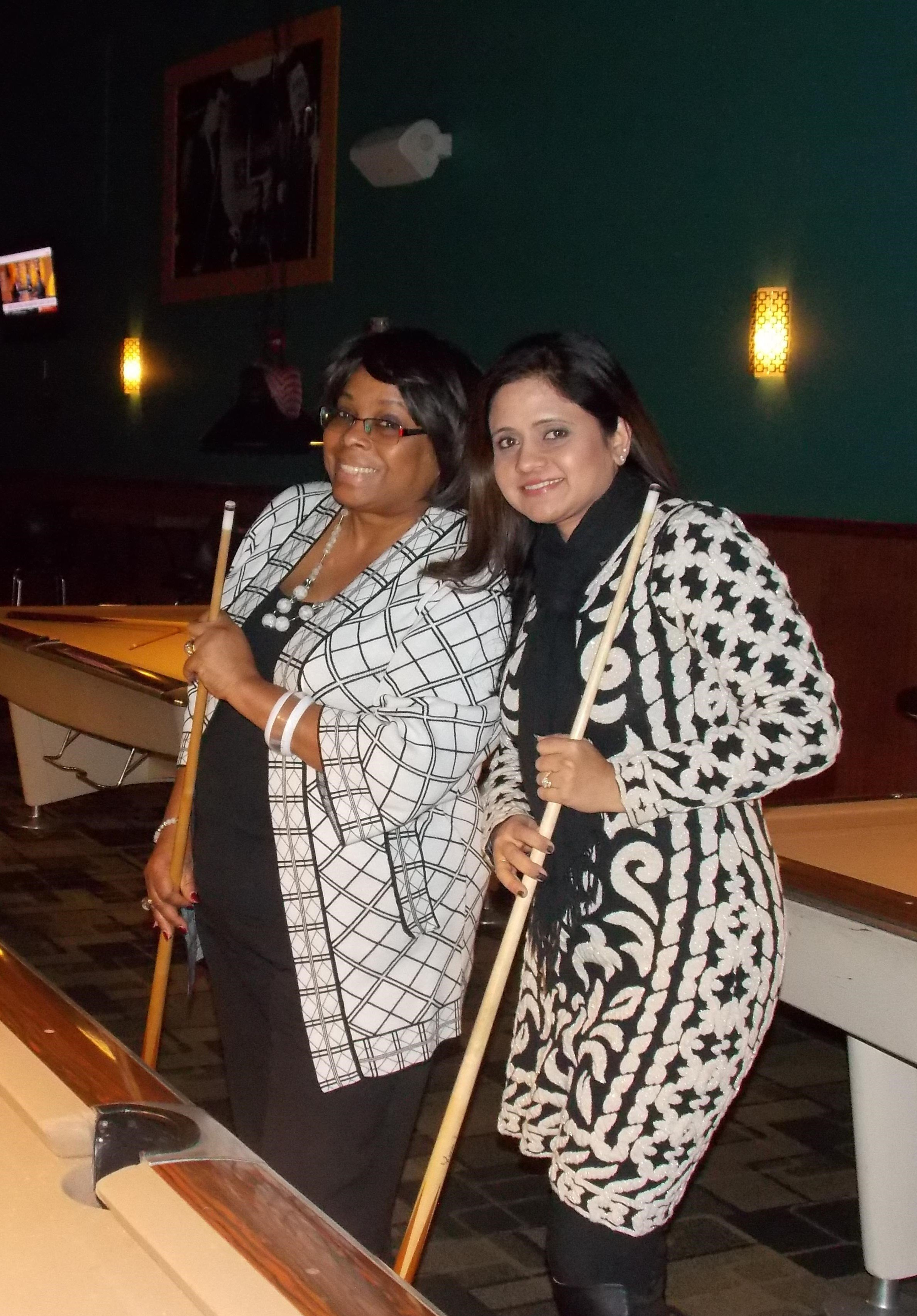 Seniorlink employees smiling while playing a game of pool